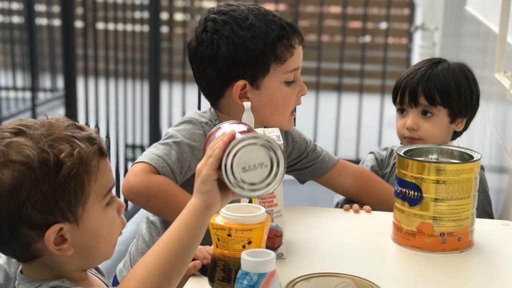 crianças brincando com latas de leite na escola